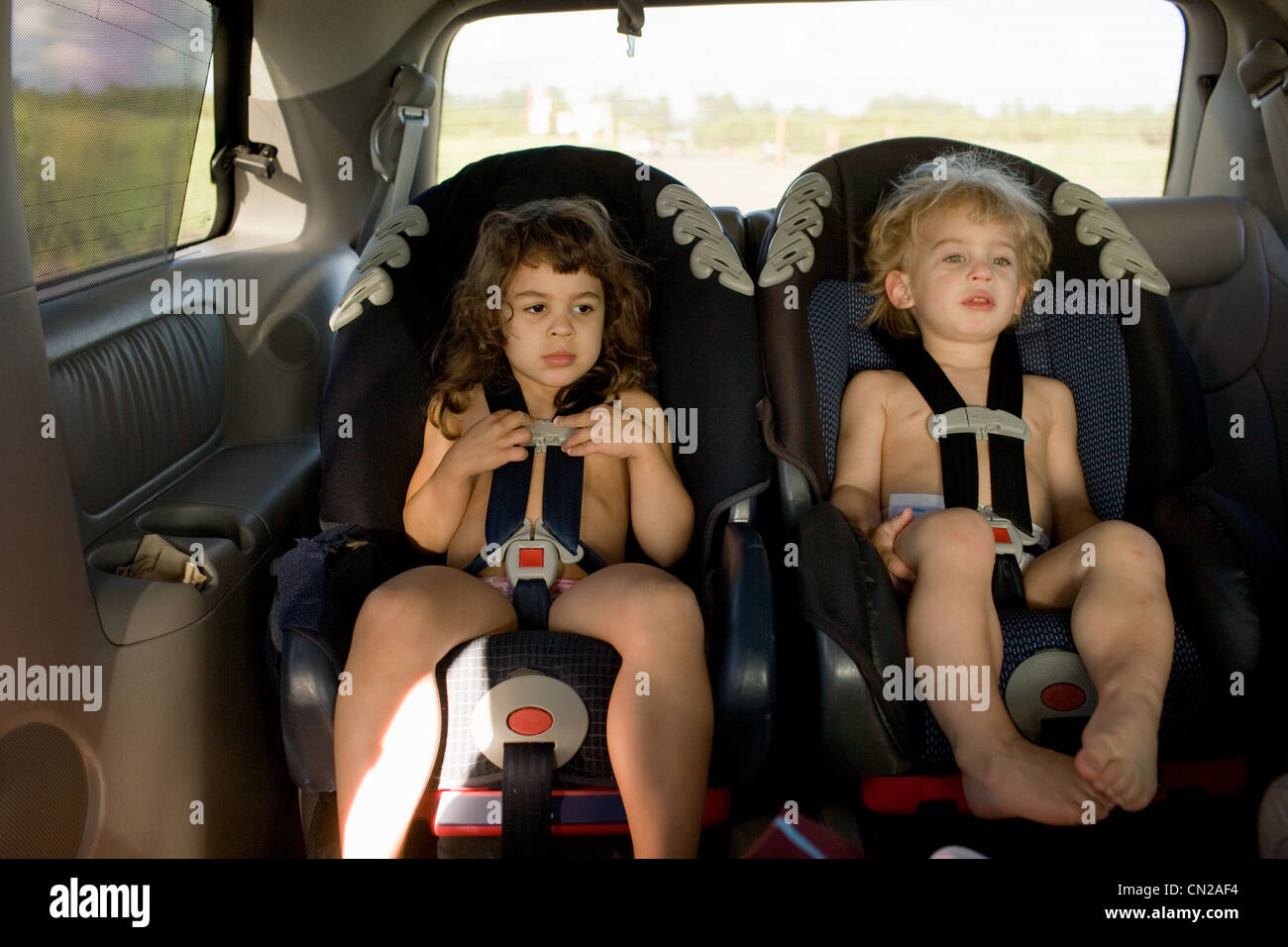 Brother and sister sitting in car seats - Stock Image
