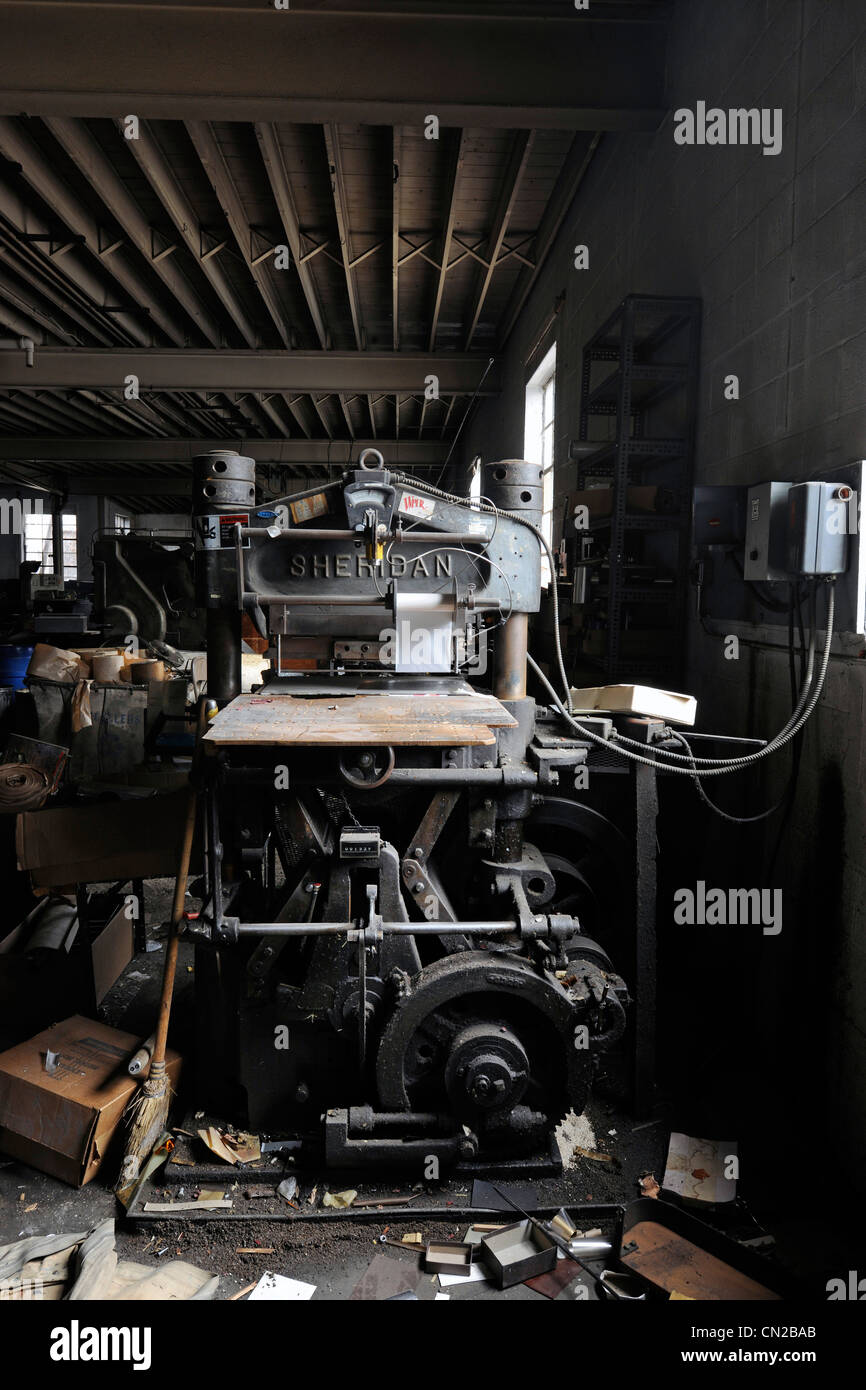 Old printing press machine in building in bankruptcy proceeding. - Stock Image