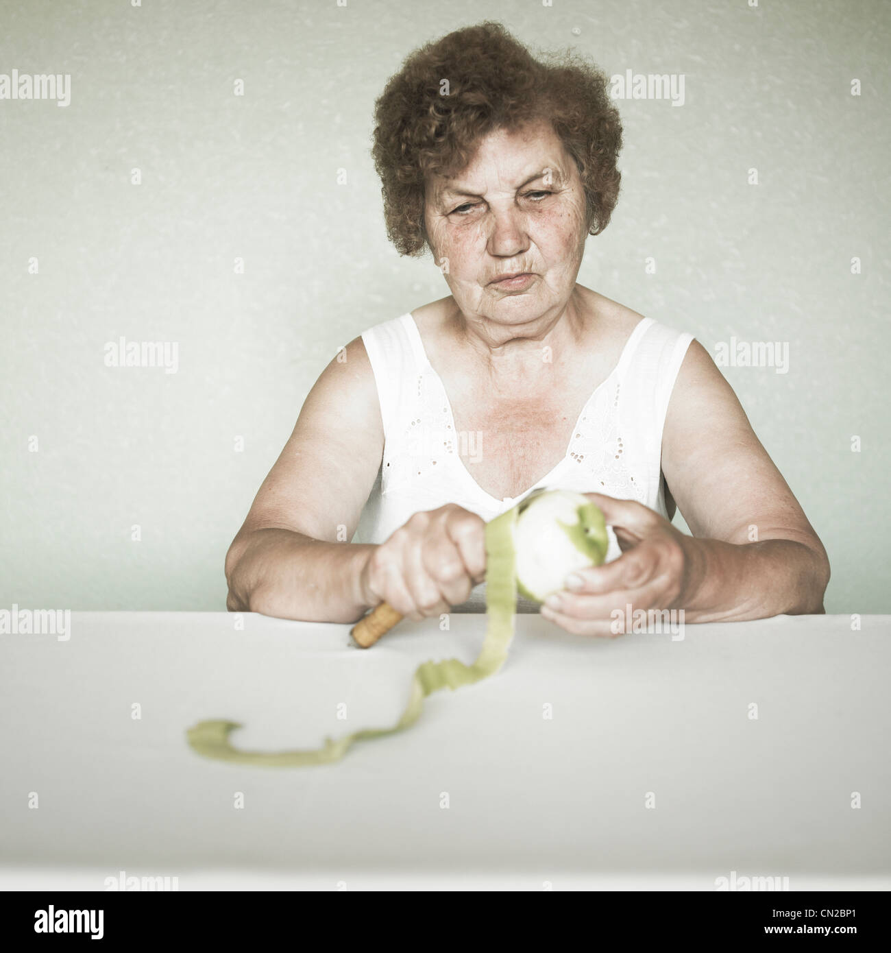 Gracious senior lady portrait cleaning an apple - Stock Image