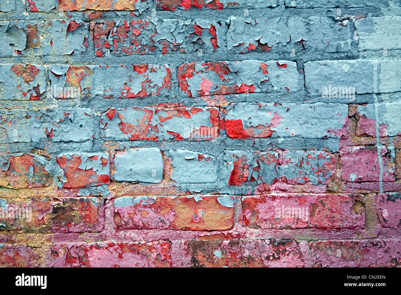 Colorful Peeling Paint on Brick Wall - Stock Image