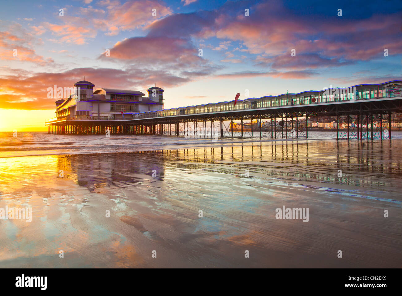 Sunset over the Grand Pier at Weston-Super-Mare, Somerset, England, UK reflected in the wet sand of the beach at - Stock Image