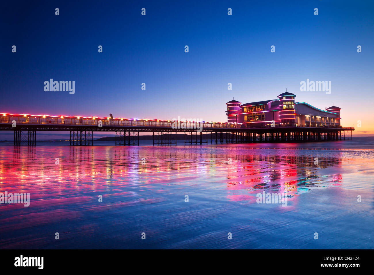 Twilight over the illuminated Grand Pier at Weston-Super-Mare, Somerset, England, UK reflected in wet sand at high - Stock Image