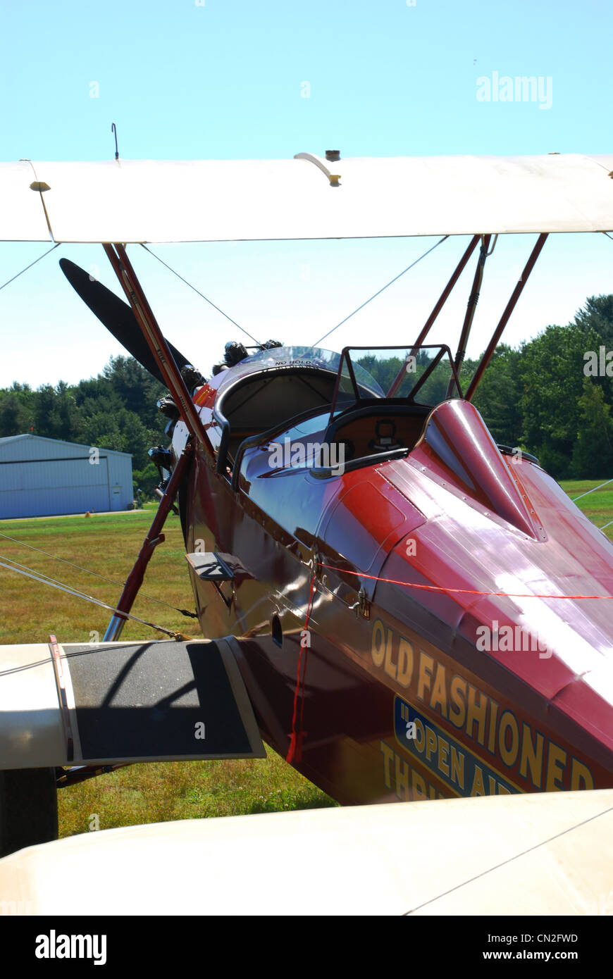 Biplane at an old fashioned airfield. This maroon fabric covered aircraft is used to give pleasure rides at Hampton - Stock Image