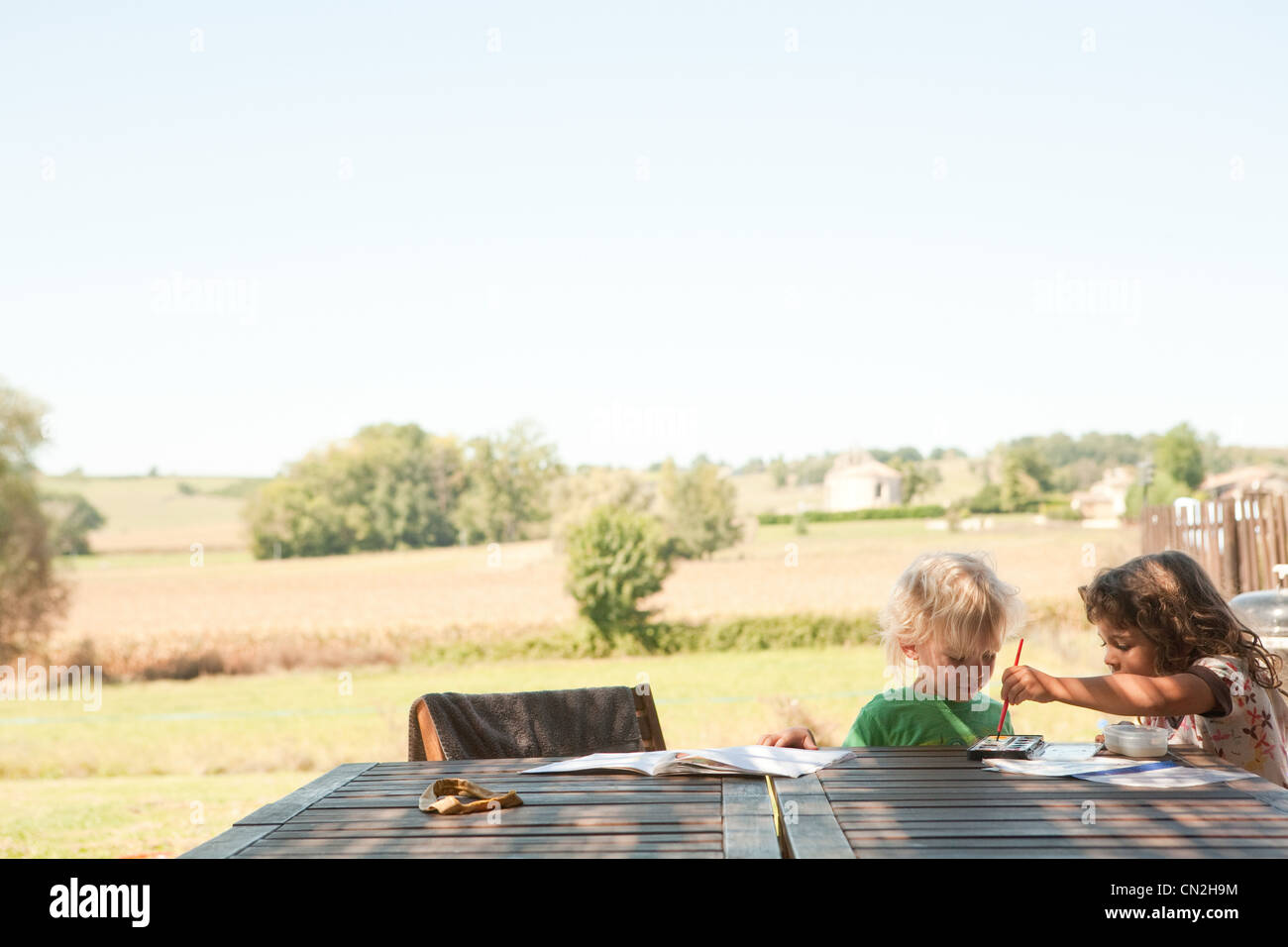 Brother and sister painting outside - Stock Image