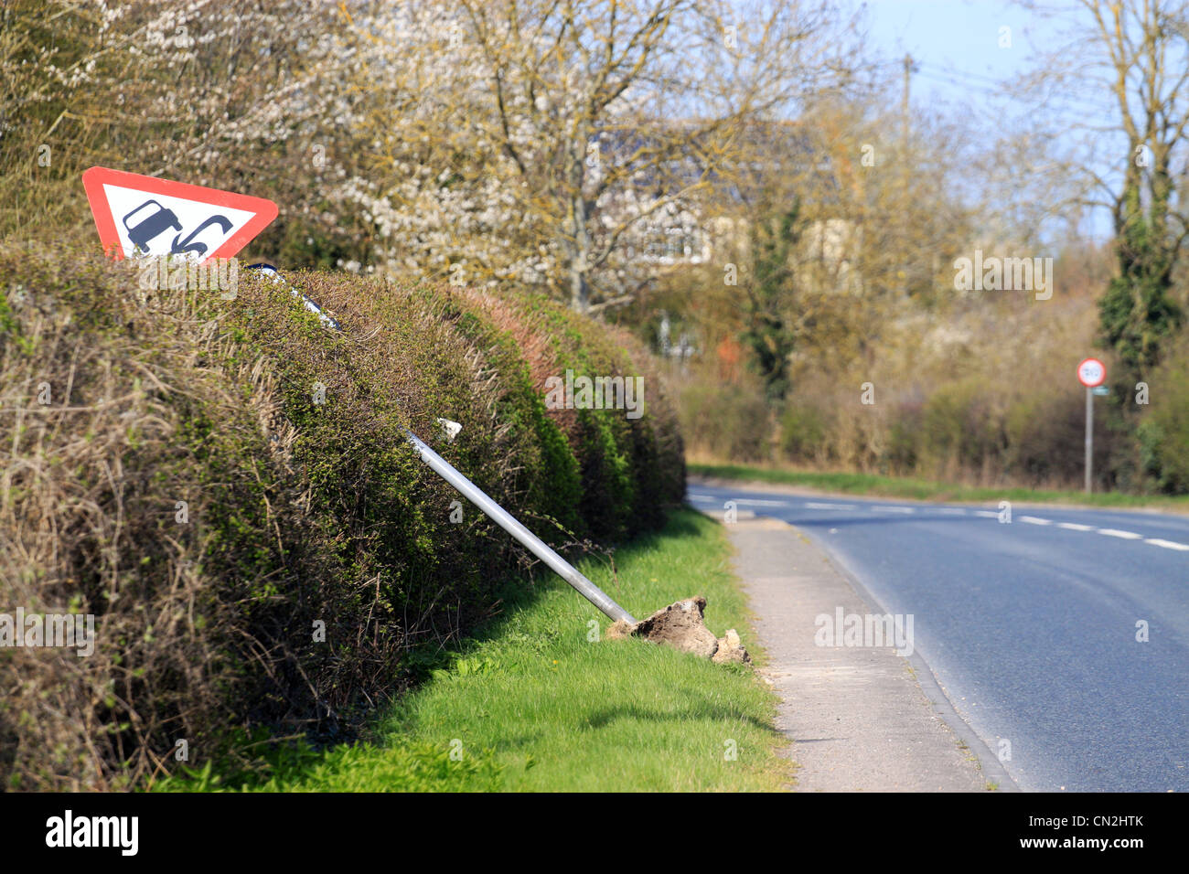 slippery road sign that has been knocked down by a car - Stock Image