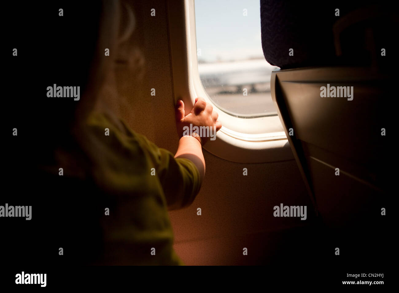 Toddler boy looking through airplane window - Stock Image