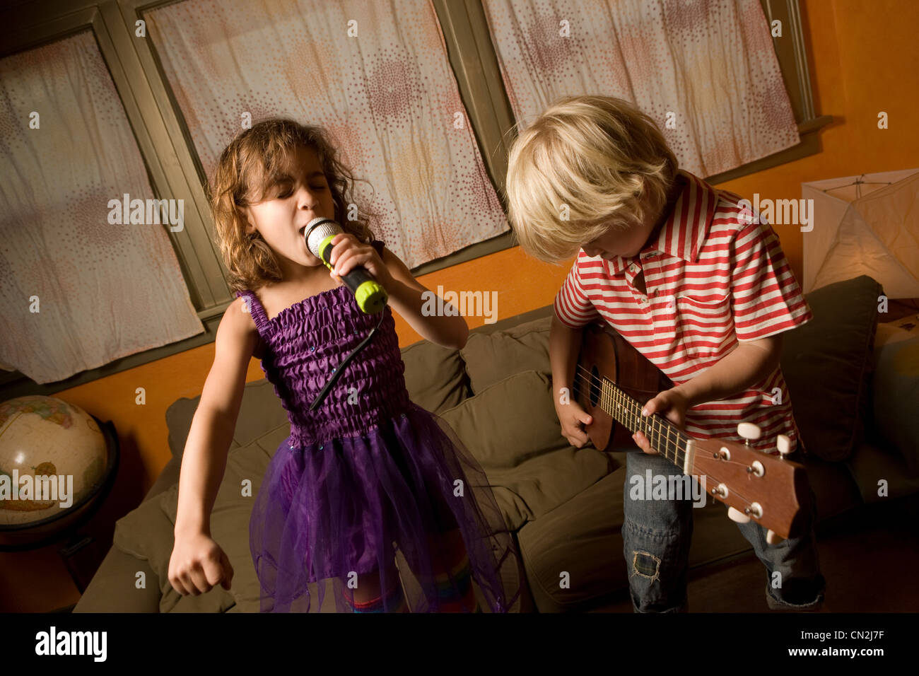 Girl singing with microphone with boy playing guitar - Stock Image