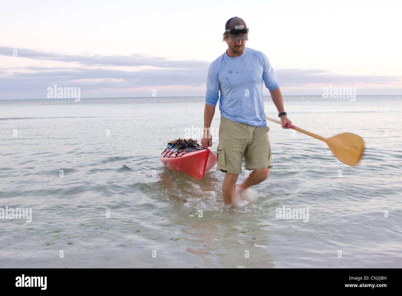 Man Pulling Kayak onto Beach, Florida Keys, USA - Stock Image
