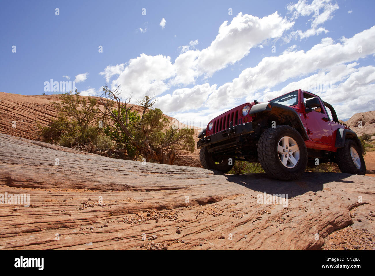 Jeep Driving on Red Rocks, Low Angle View, Moab, Utah, USA - Stock Image