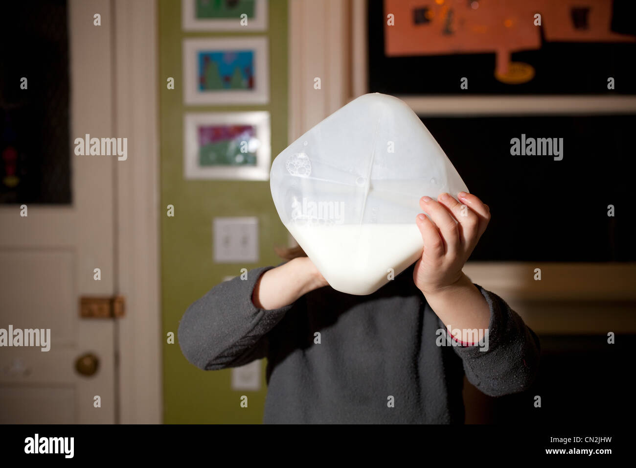 Boy drinking milk from container - Stock Image