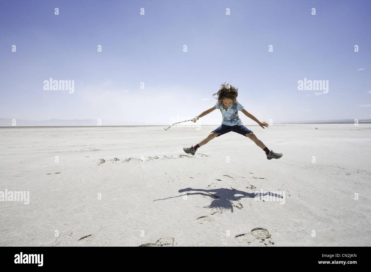 Young Girl Jumping Over Name Scratched into Salt Lake, Utah, USA - Stock Image