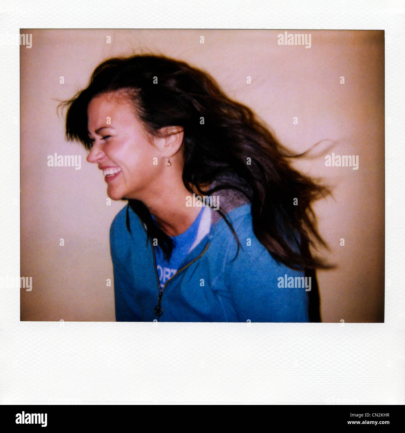 Instant film photograph of young woman laughing - Stock Image