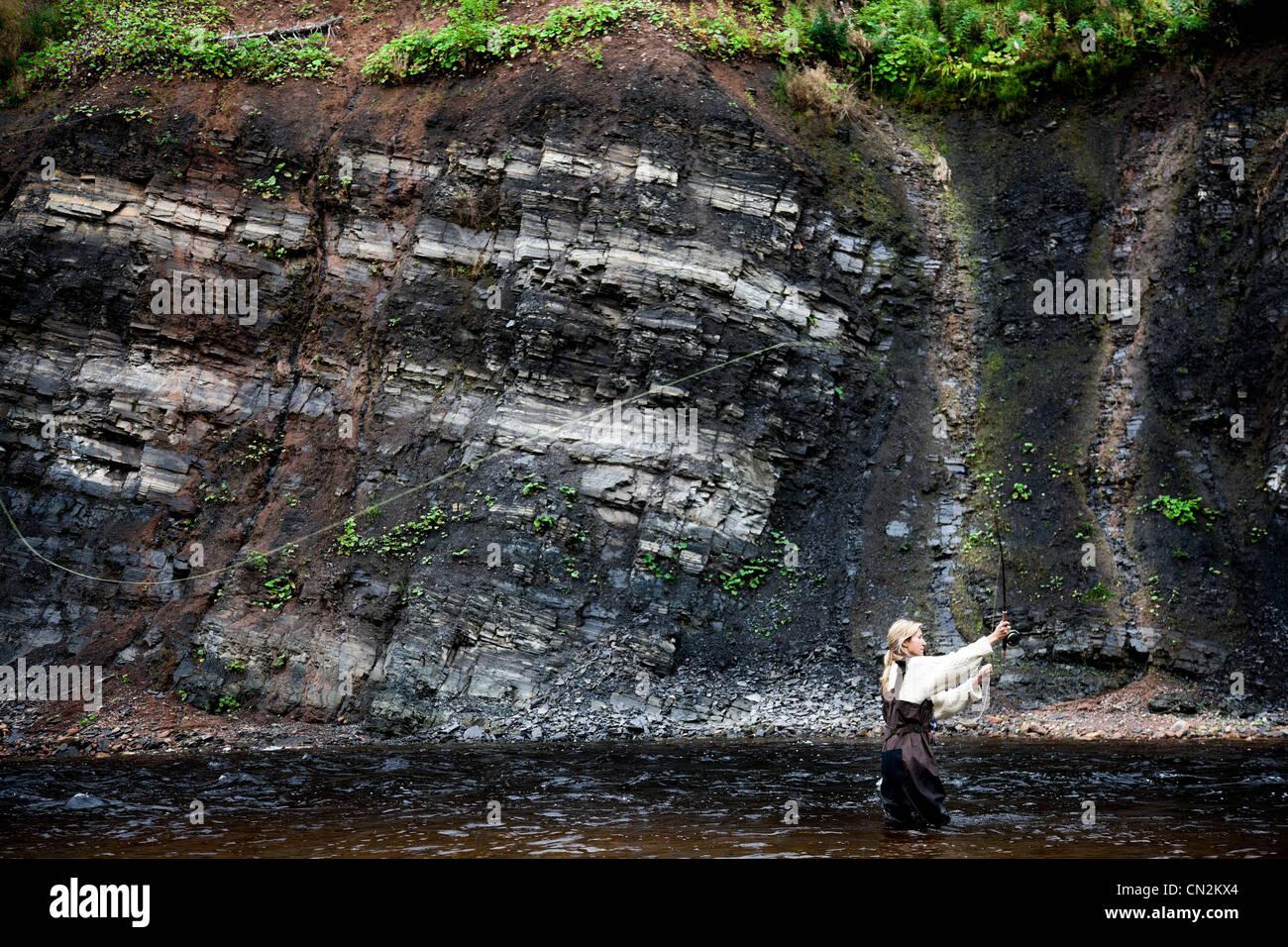 Female fly fisher in Margaree River, Cape Breton Island, Nova Scotia - Stock Image