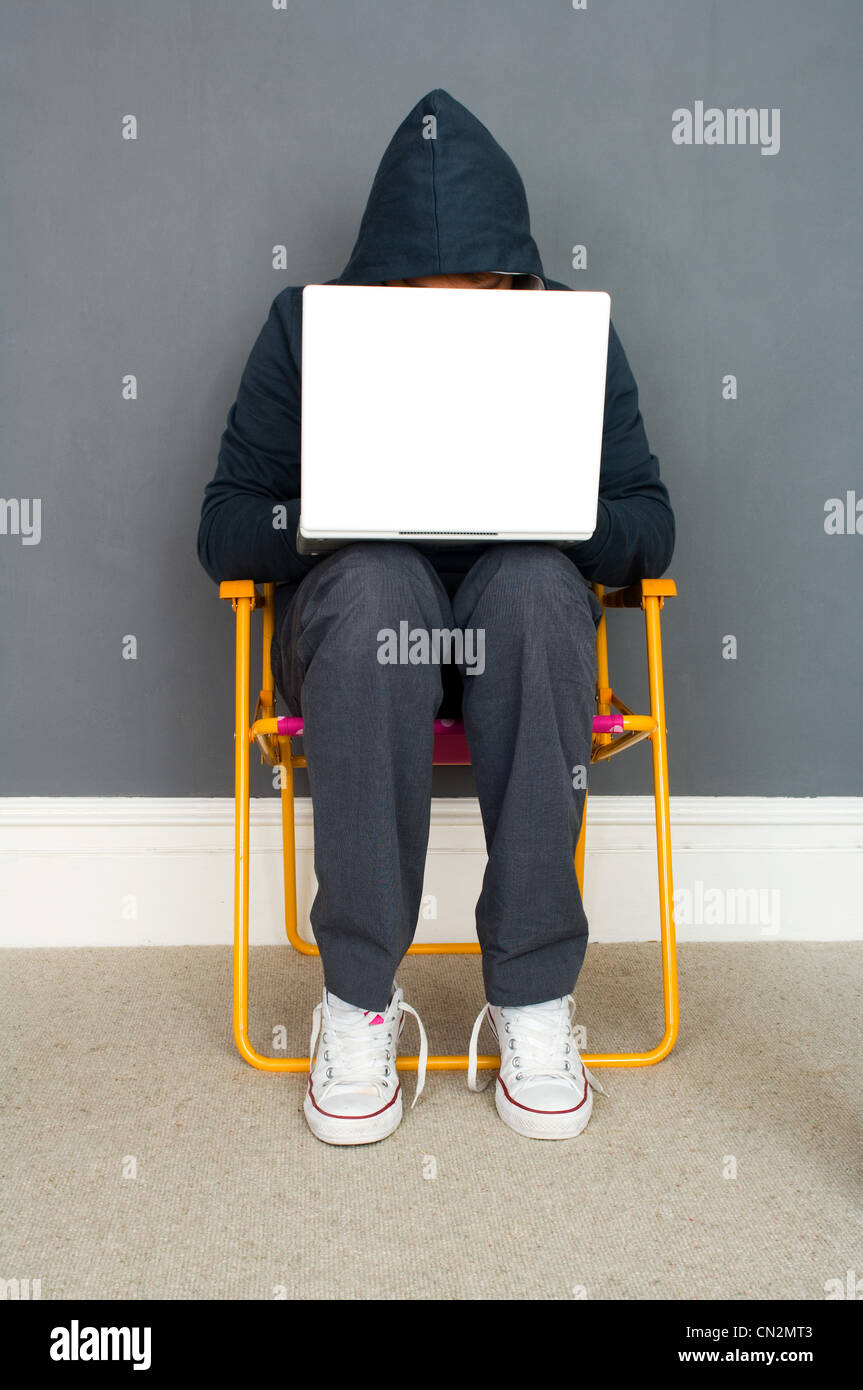 Young man wearing hooded top using laptop - Stock Image