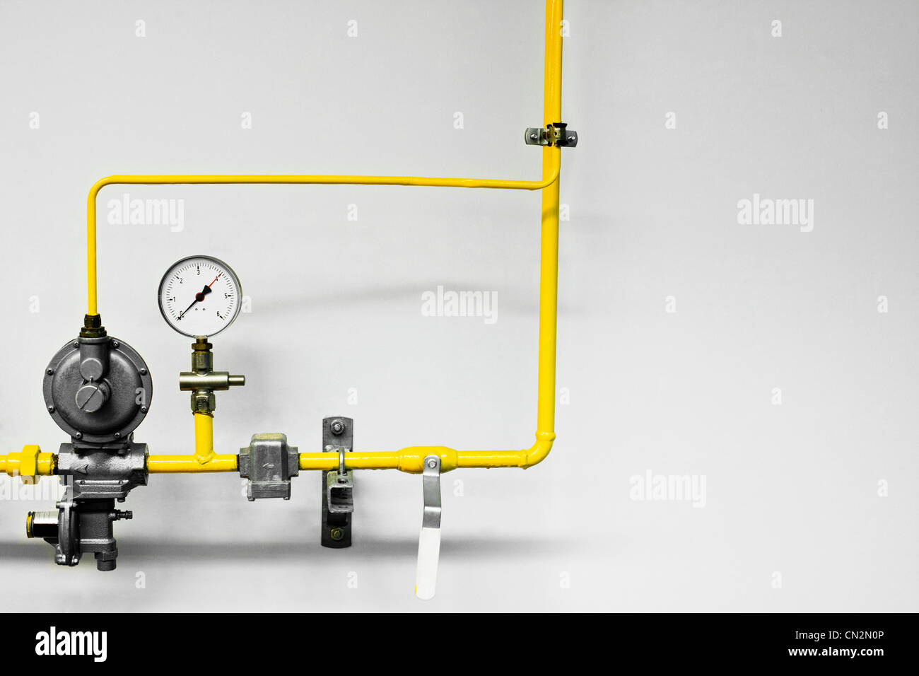 Yellow industrial pipes and pressure guage - Stock Image