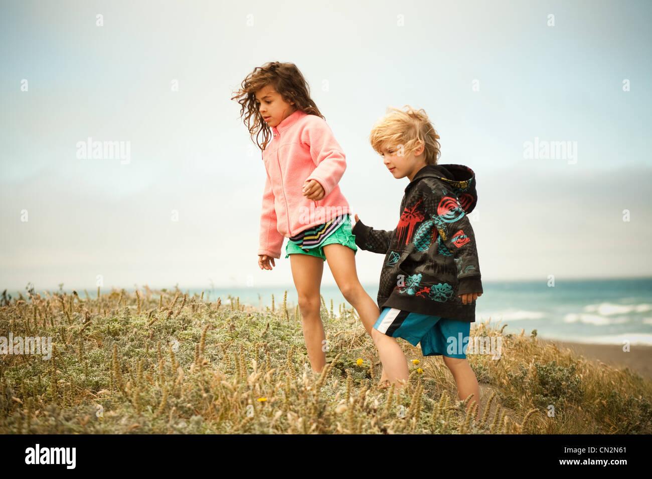Two children walking along coast - Stock Image