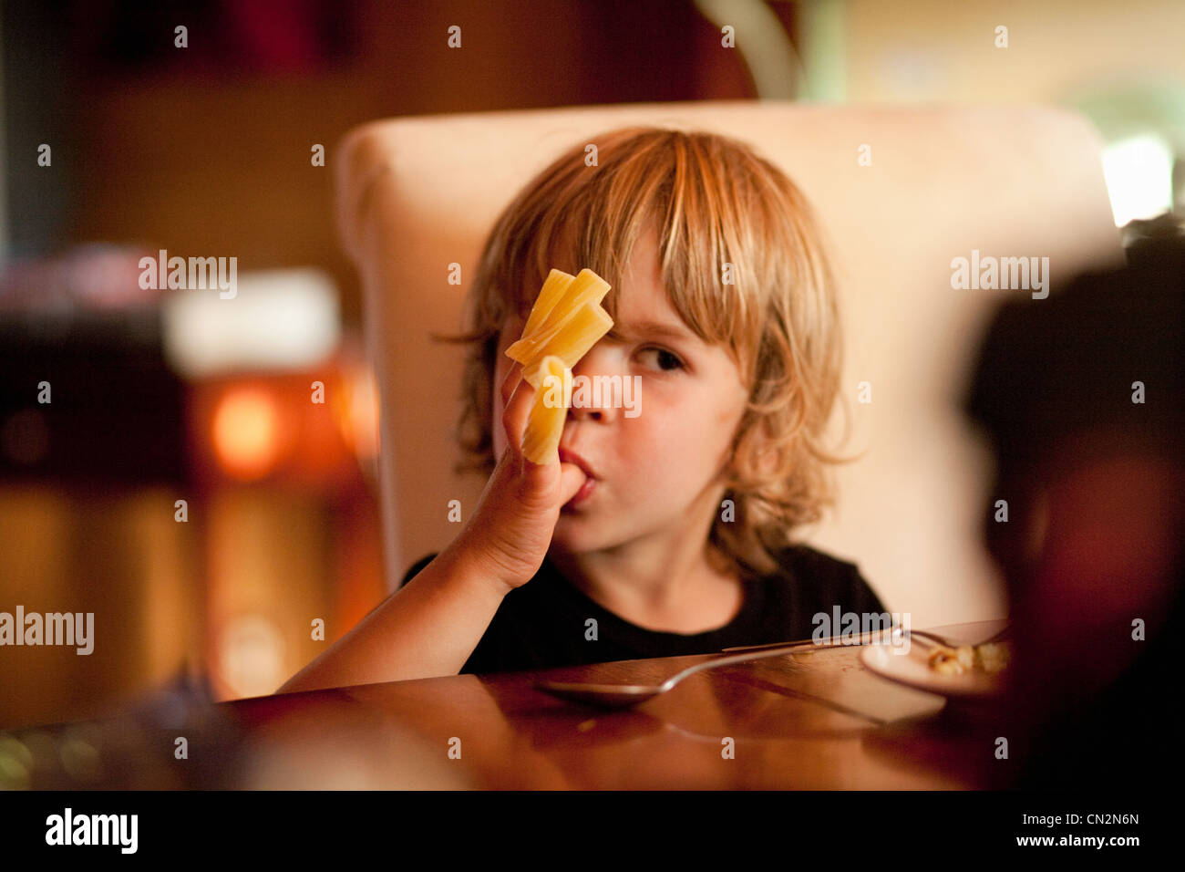 Boy eating pasta off fingers - Stock Image