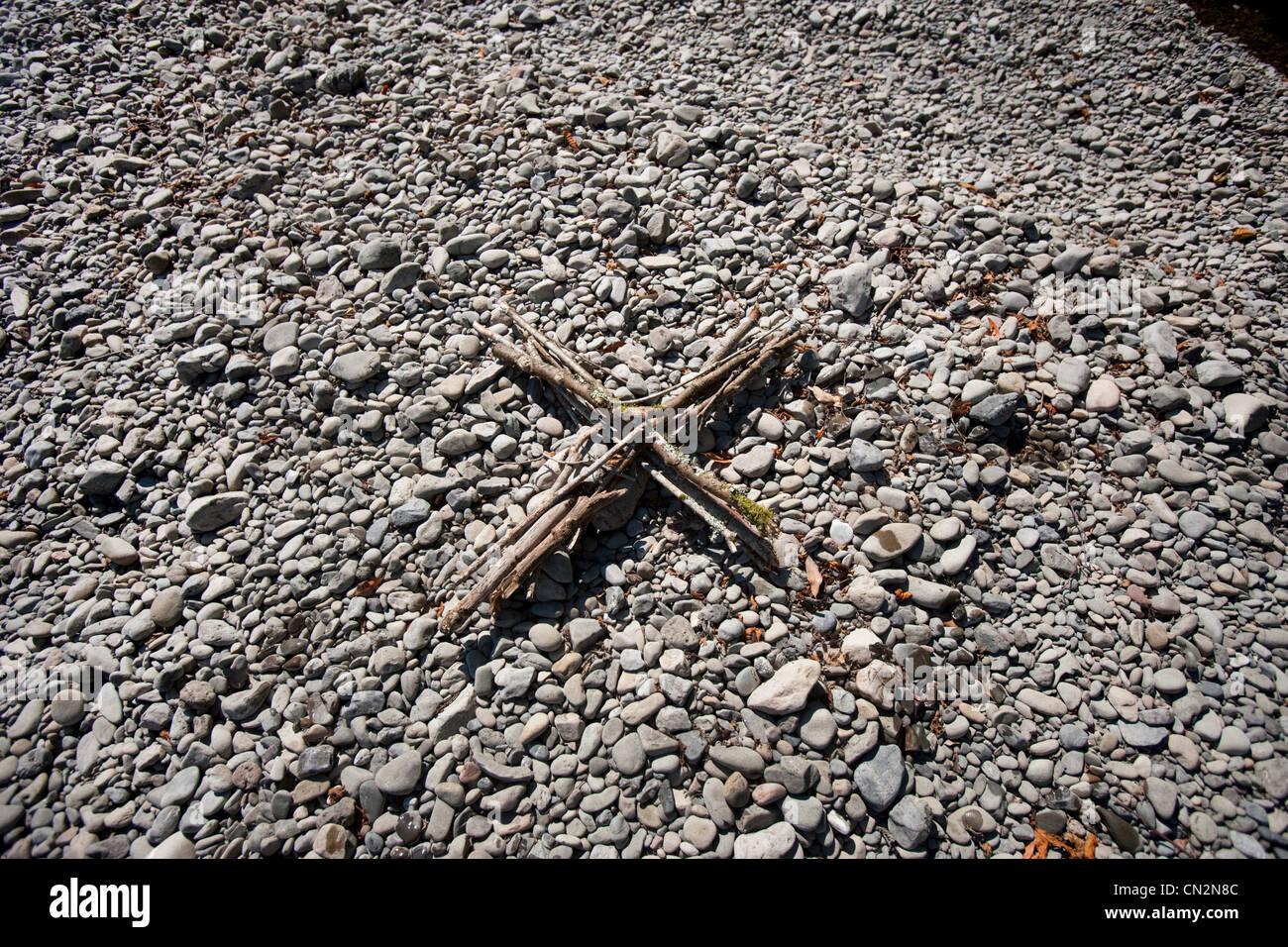 Sticks in cross shape on pebbles - Stock Image