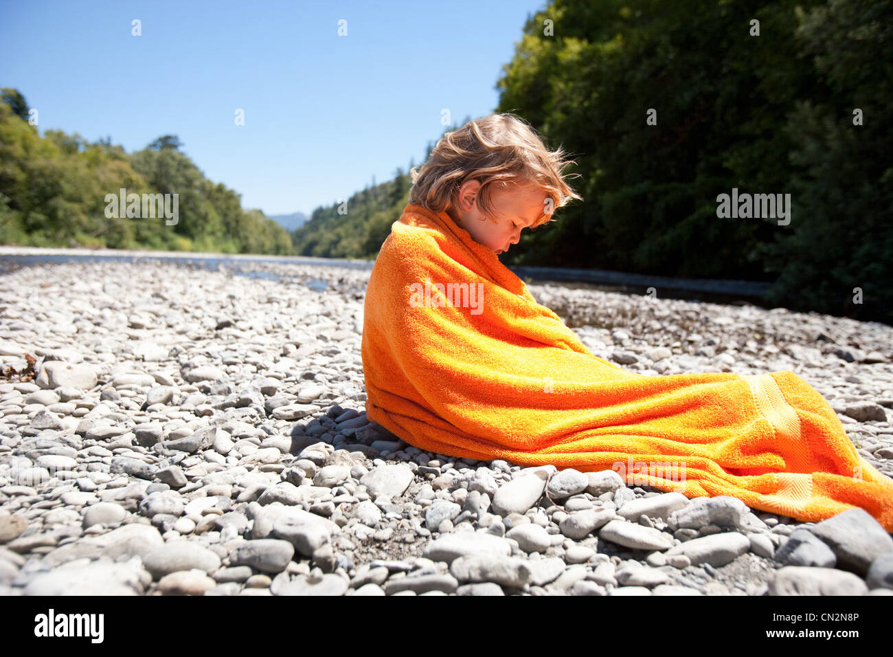 Boy wrapped in towel sitting on rocks - Stock Image