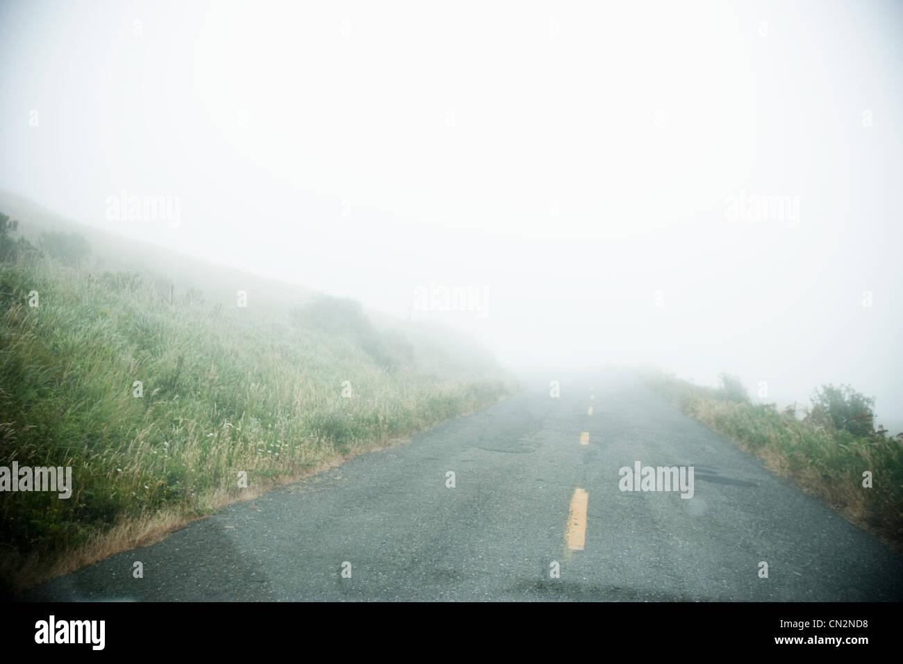 Foggy road through car windscreen - Stock Image