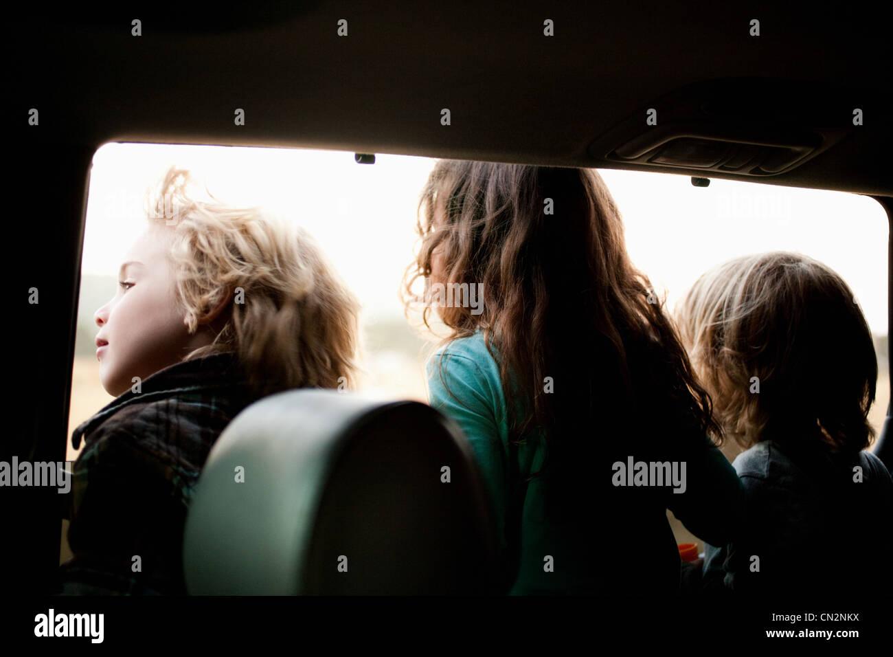 Three children looking through car window - Stock Image