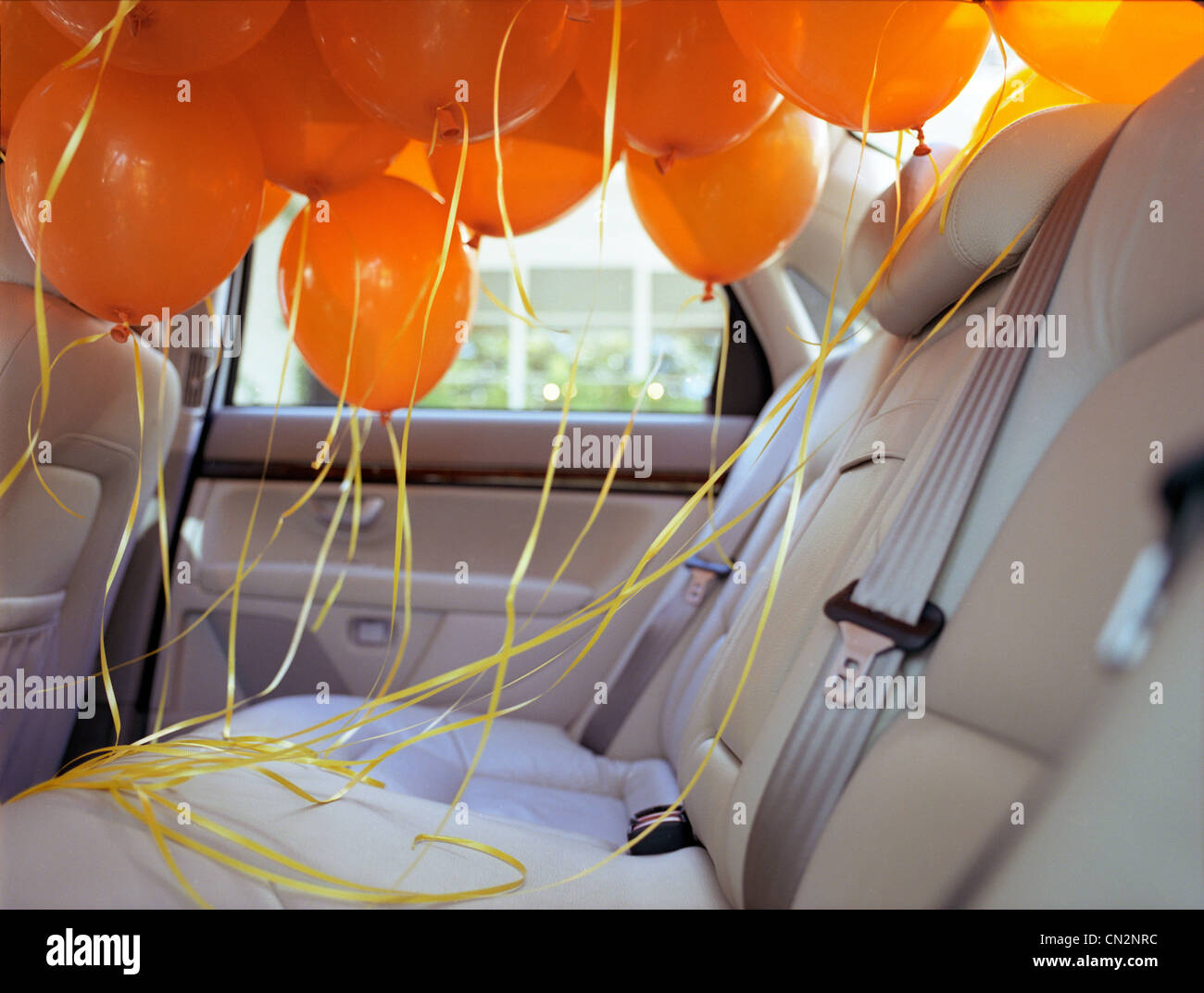 Orange balloons in back seat of car - Stock Image