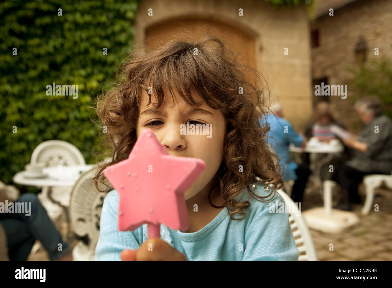 Girl eating star shaped ice cream Stock Photo