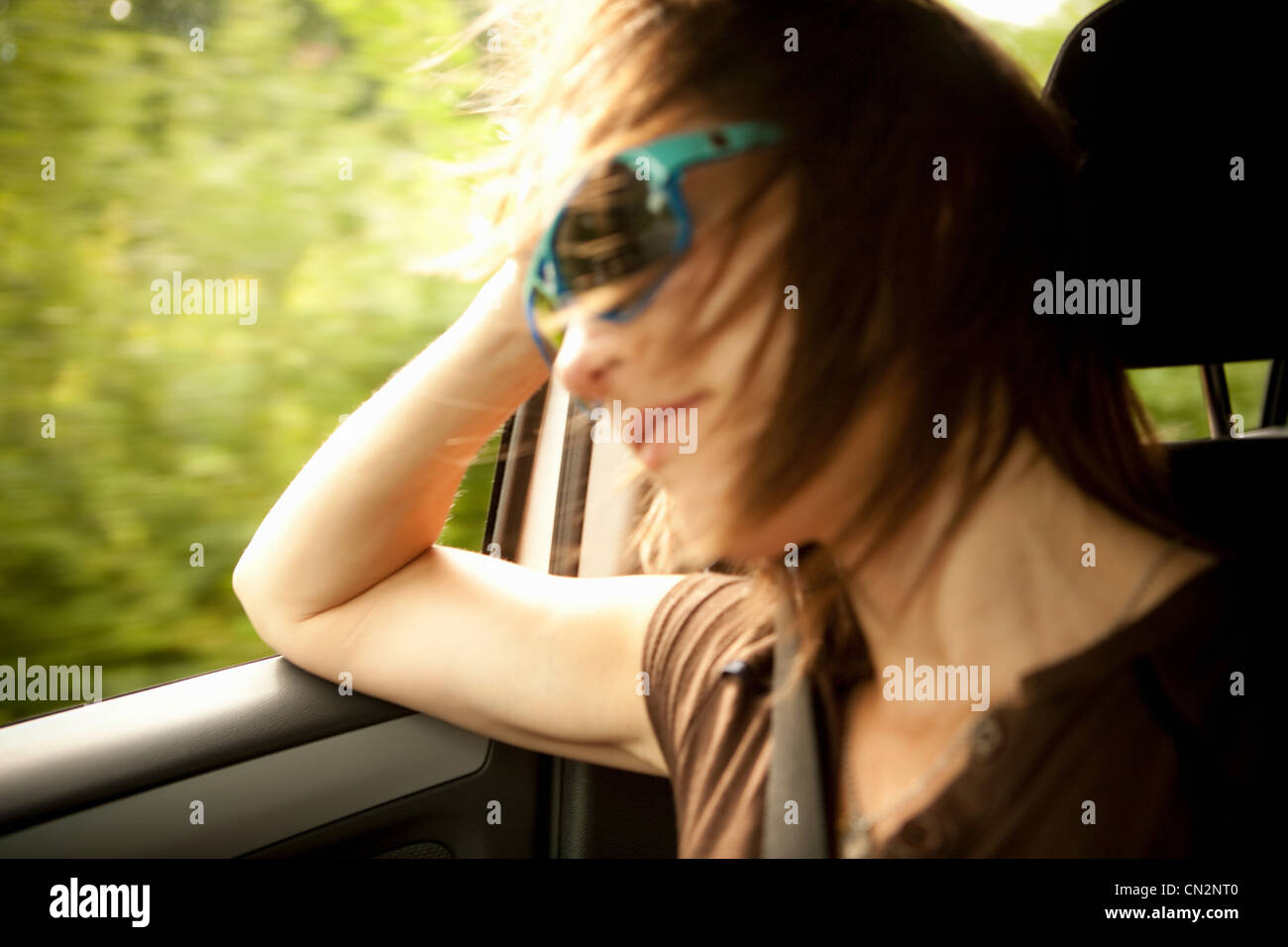 Female passenger in car with window open - Stock Image