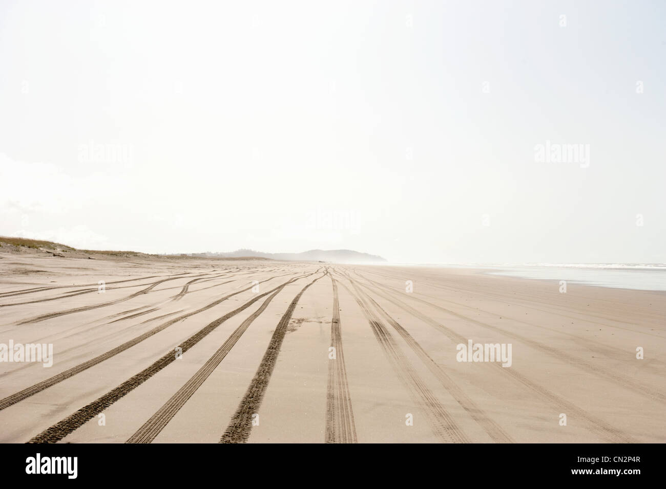 Boy on sandy beach with tire tracks - Stock Image