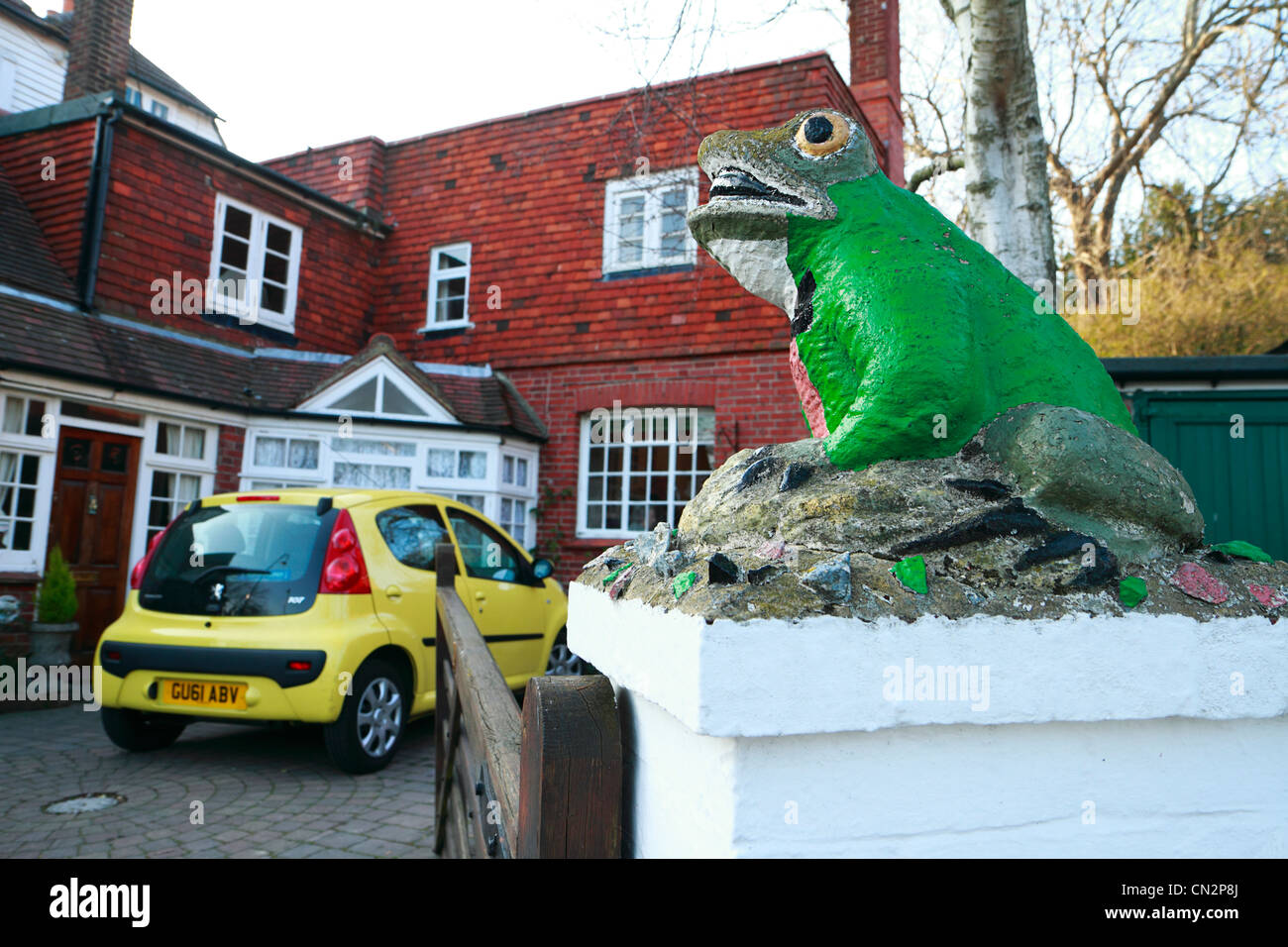 Painted stone toad on gatepost of house, Bexhill, East Sussex, UK - Stock Image