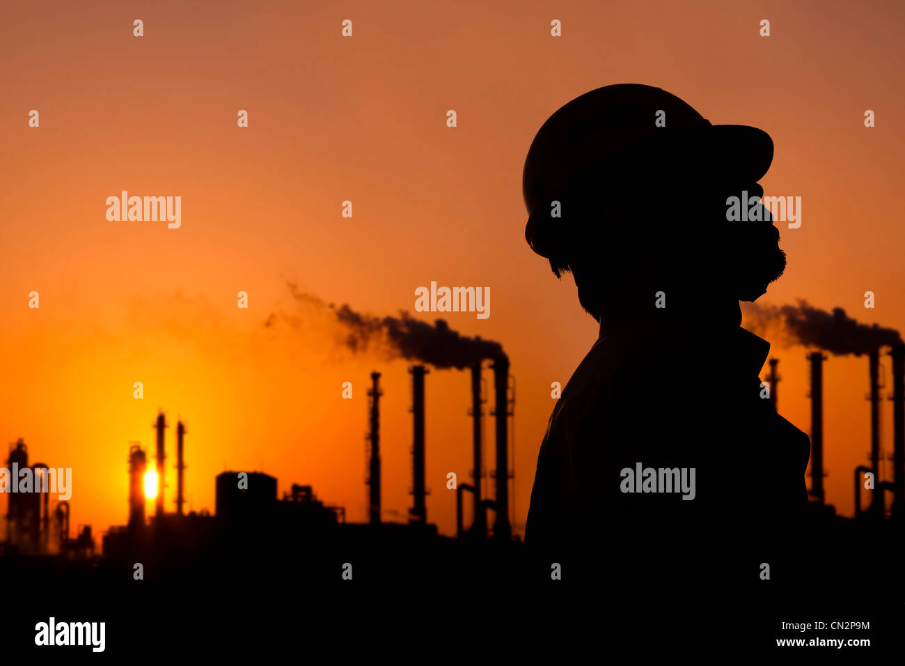 the silhouette of oil refinery worker at sunset - Stock Image