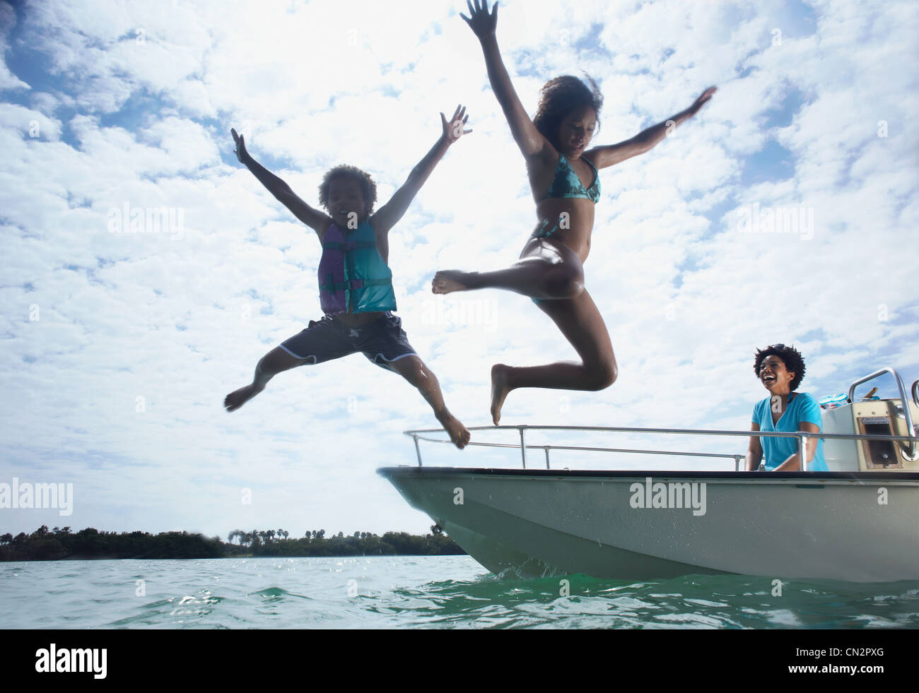 Mother on motorboat, two children jumping into water Stock Photo