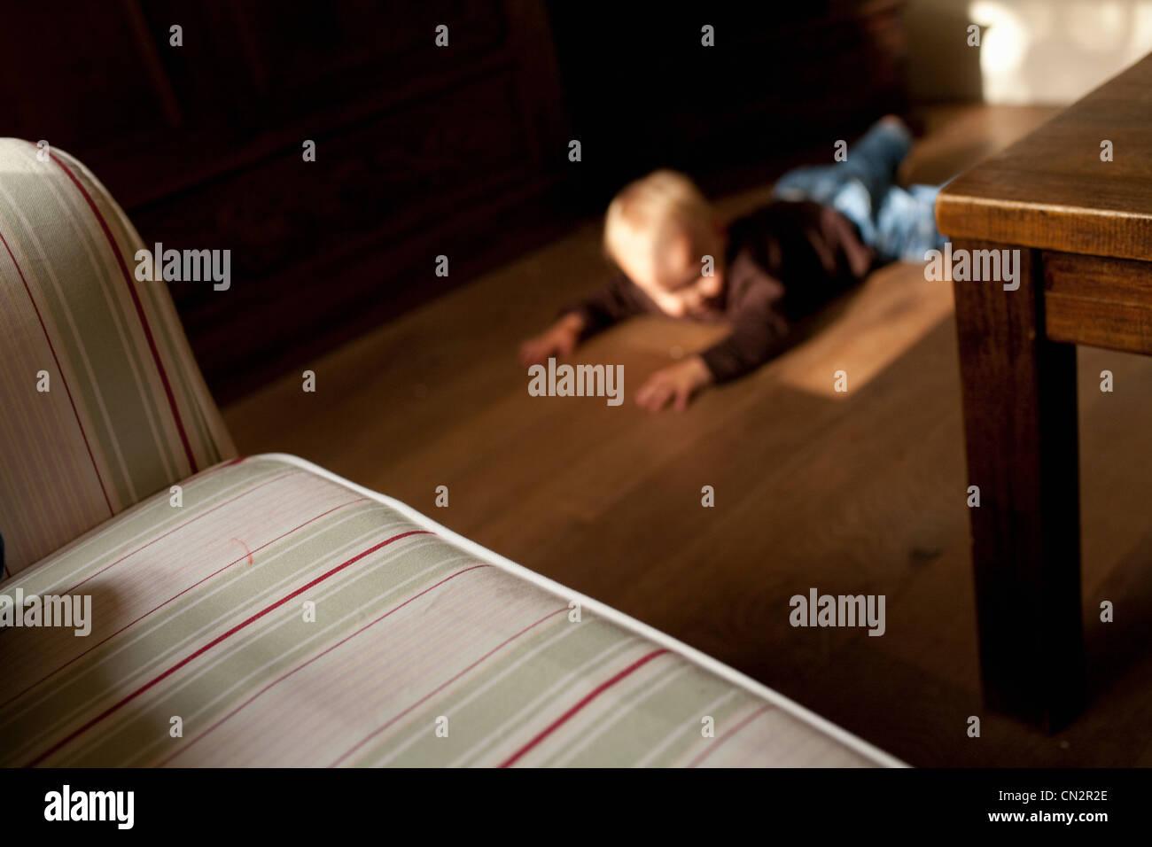 Toddler boy lying on floor - Stock Image