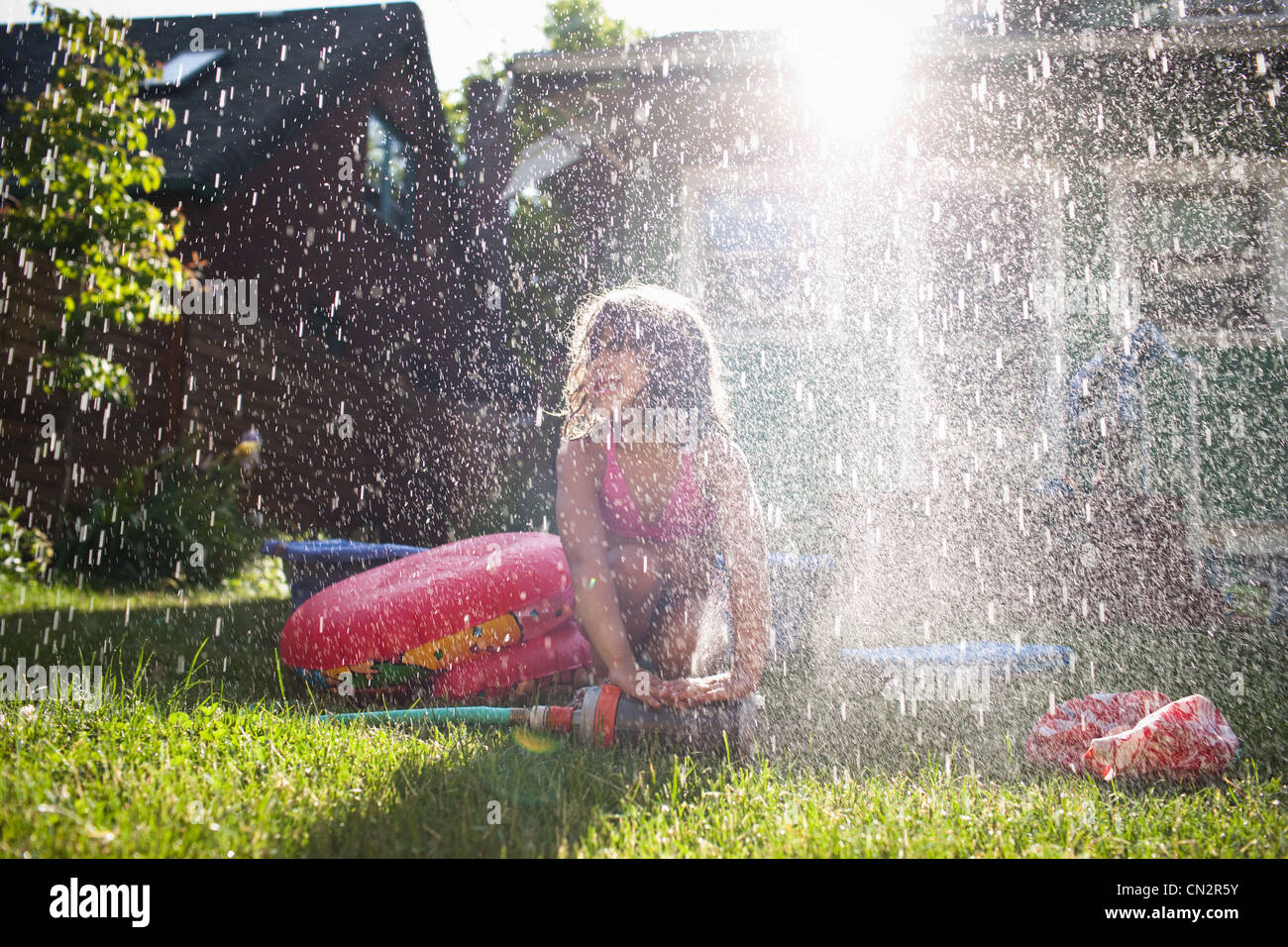 Young girl playing in garden sprinkler - Stock Image