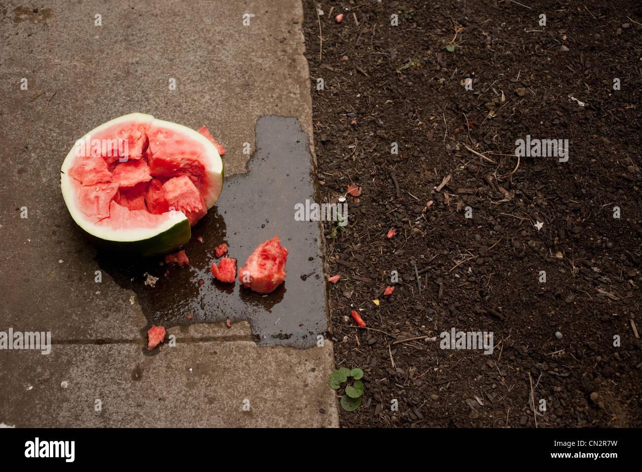 Broken watermelon on sidewalk - Stock Image