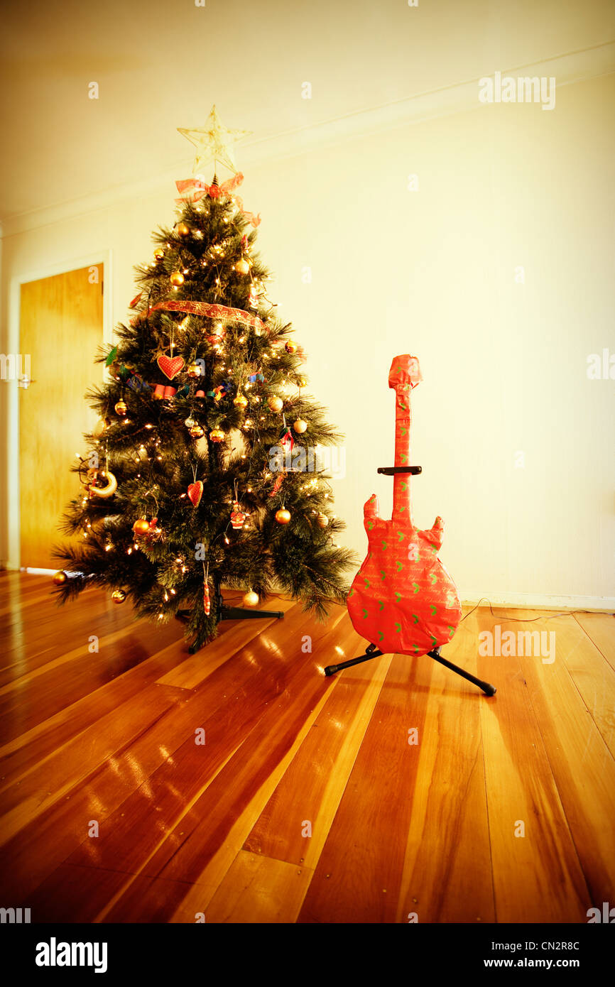 Chrismas wrapped guitar present and tree. - Stock Image