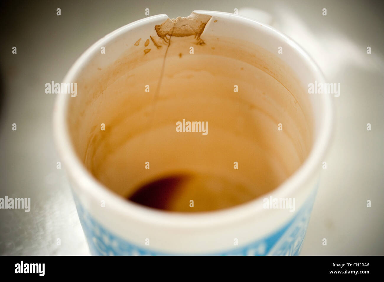 Dirty cracked mug - Stock Image