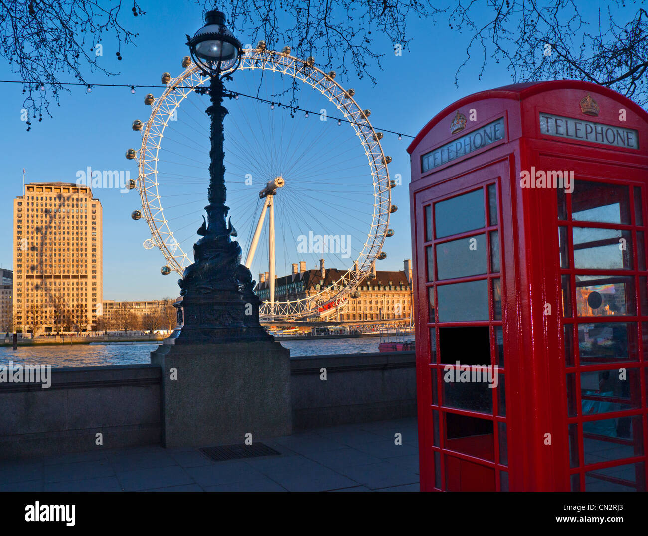 Traditional red telephone kiosk at Westminster Pier with River Thames and London Eye behind at sunset London UK - Stock Image