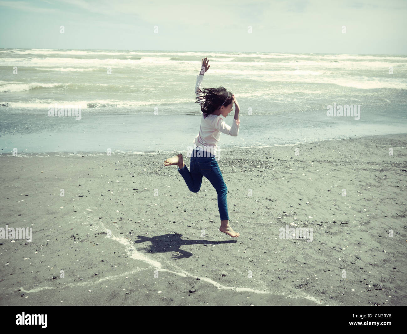Girl jumps at beach. - Stock Image