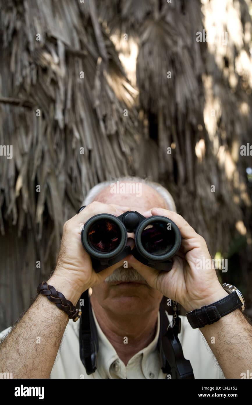Elderly Man Looking Through Binoculars - Stock Image