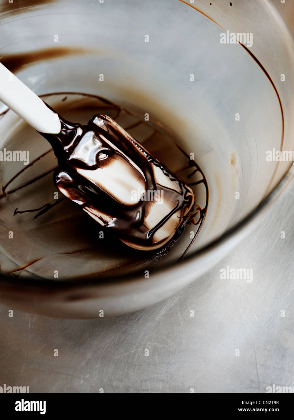 Melted dark chocolate in mixing bowl with spatula - Stock Image