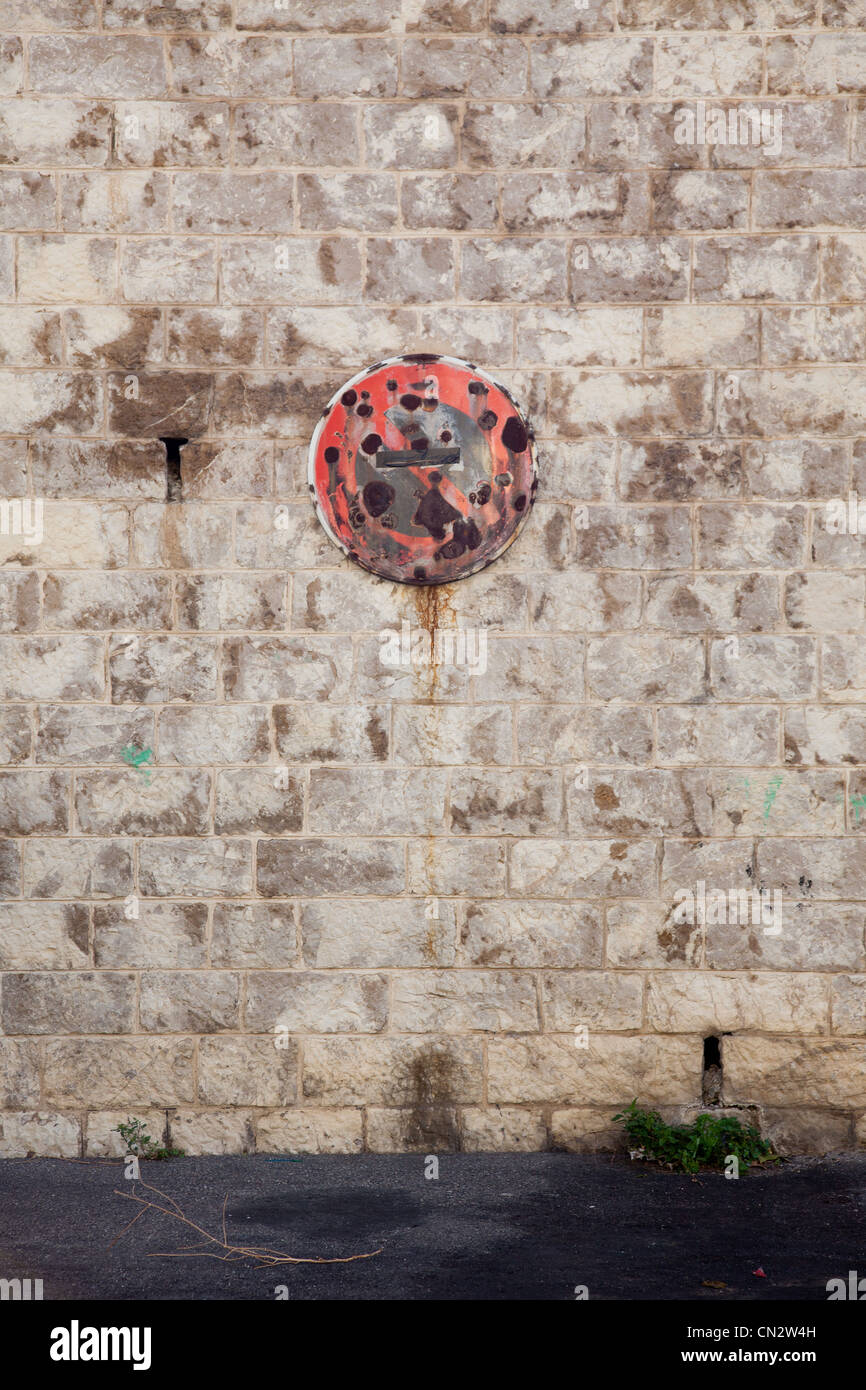 Rusty no parking sign on stone wall - Stock Image