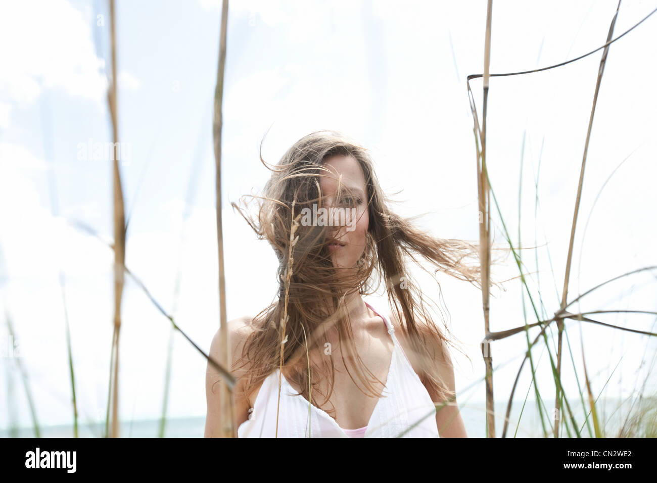 Young woman in grass with tousled hair - Stock Image