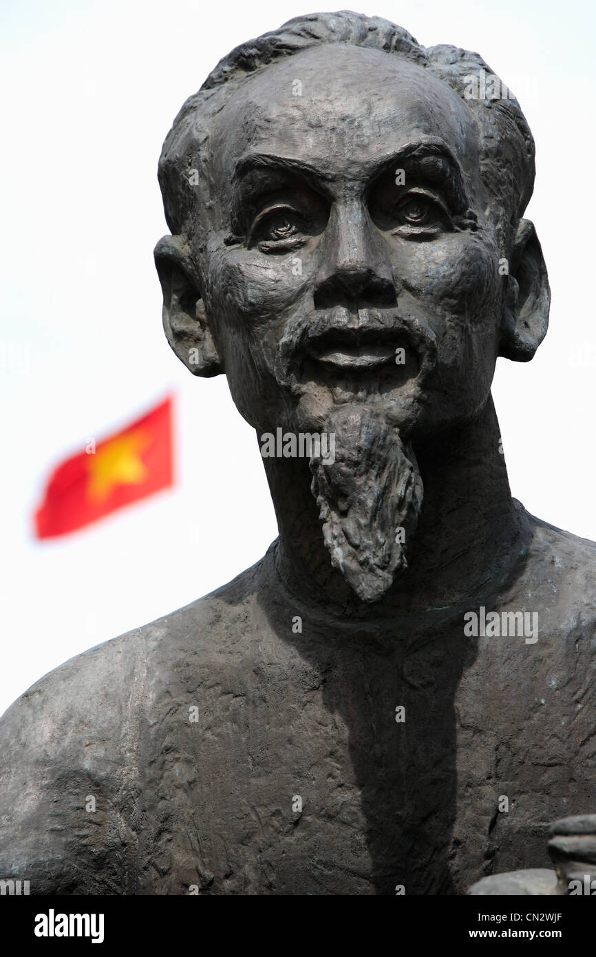Statue of Ho Chi Minh with Vietnamese flag in background - Stock Image
