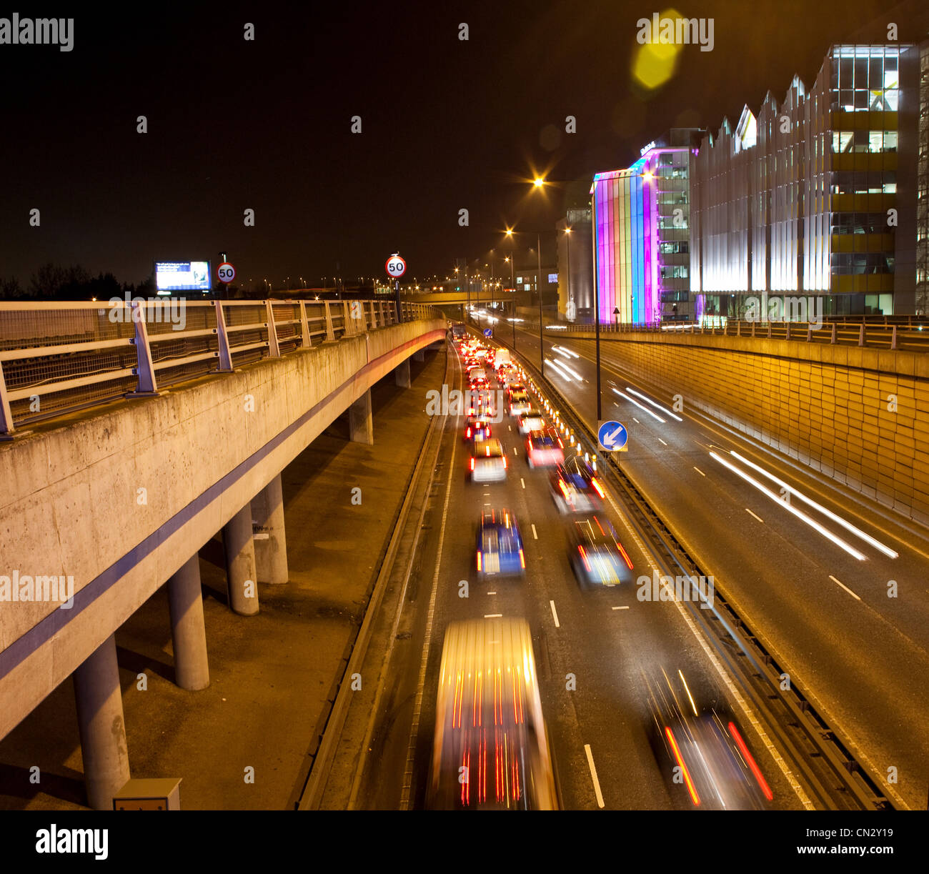 Traffic on road in urban scene at night, London, England - Stock Image