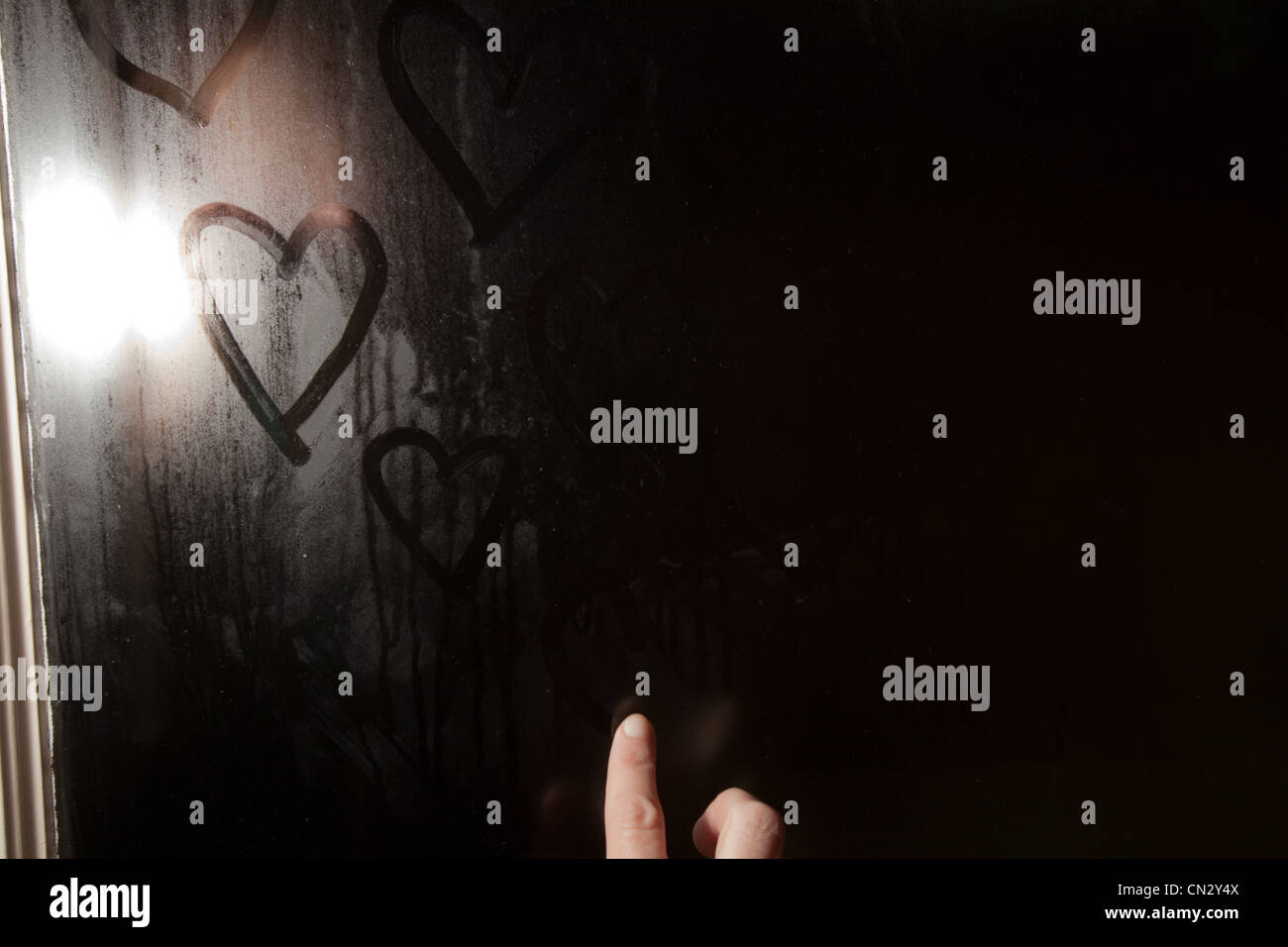 Girl drawing heart shape in condensation on window - Stock Image