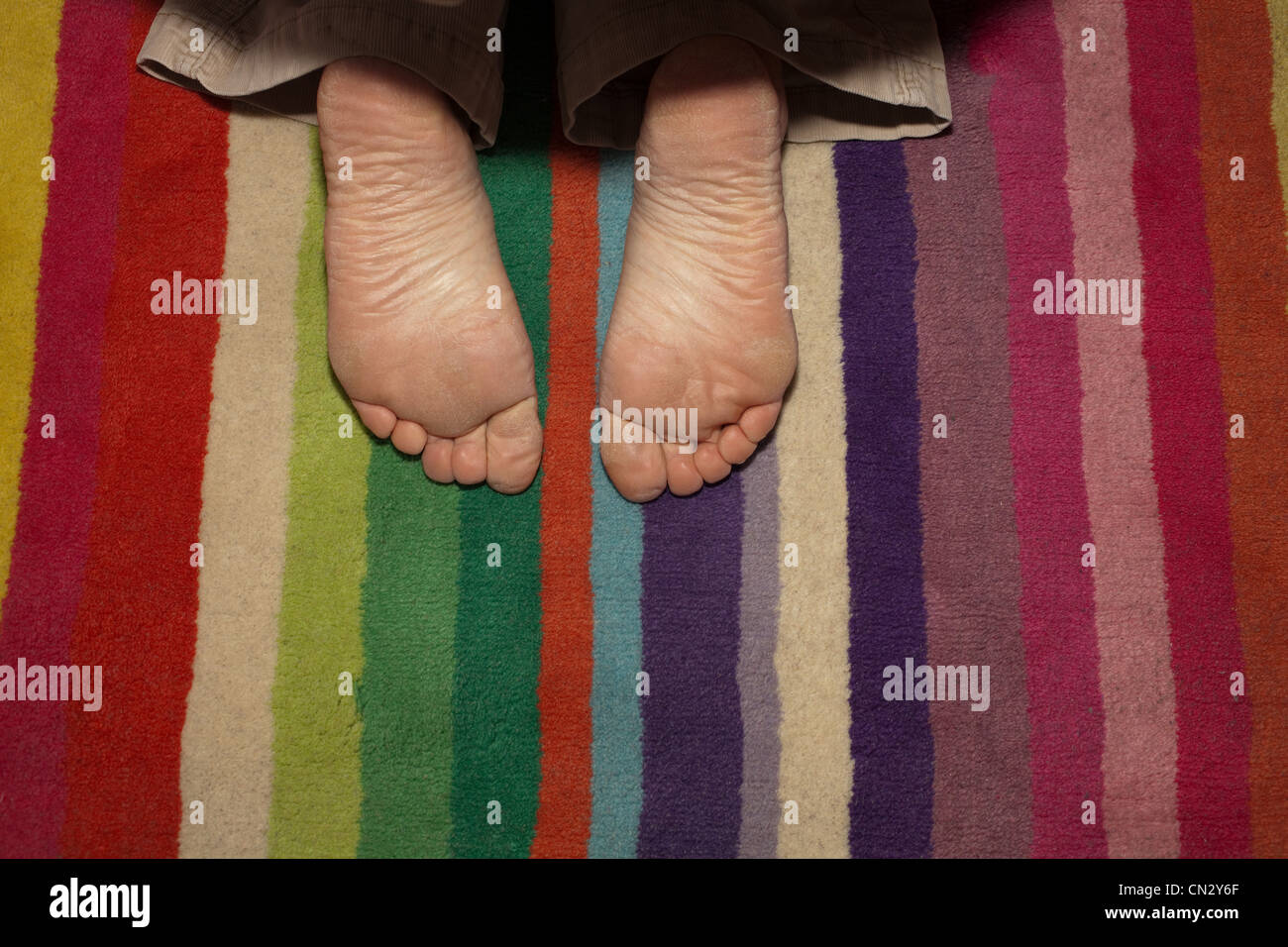 Child's feet on striped rug - Stock Image