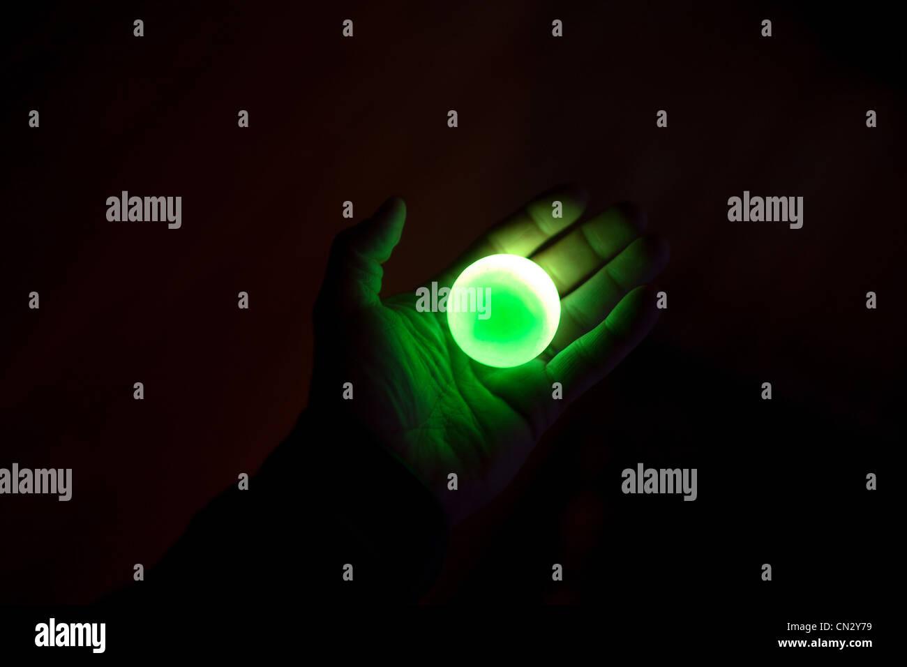 Person holding illuminated green ball - Stock Image