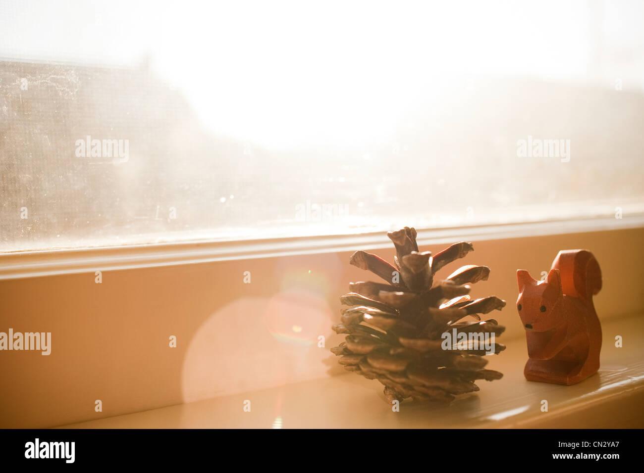 Pine cone and squirrel ornament on windowsill - Stock Image
