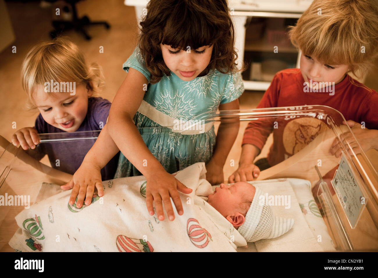 Siblings looking at newborn baby brother in hospital Stock Photo